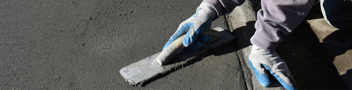 Photo of hands in gloves working on wet concrete section of a sidewalk